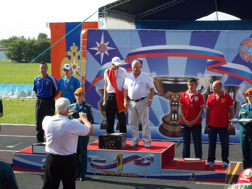 Mihkel Holzmann võtmas vastu maailmameistrivõistluste hõbemedalit. Tema kõrval noortekoondise peatreener Margo Tammepõld.